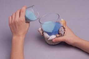 Fill the glass with the colored wax mixture.