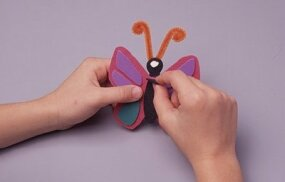 Glue the colored cutouts onto the butterfly shape.