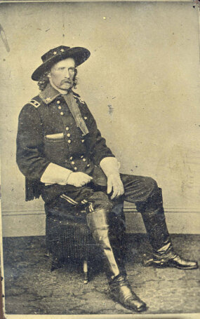 "George A. Custer in Military Dress Wearing Hat and Gloves Seated on an Ottoman,"" circa 1864."