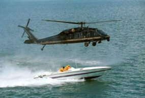 U.S. Customs agents in a Blackhawk helicopter hover over a smuggler's boat. The immense downward air pressure generated by the helicopter's propellers convinces the smugglers to stop where they are.