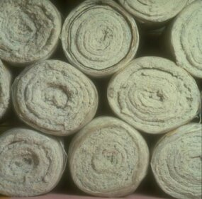 Rolls of natural cotton and recycled cotton prepared for use as an alternative to fiberglass insulation.