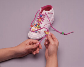 Knot the shoelace to hold bead in place.