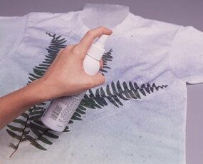Spray the paint in a diagnol movement beginning at the lower right corner of the shirt.
