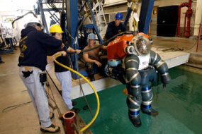 The Atmospheric Dive Suit (ADS) is lowered into the water for a dive.