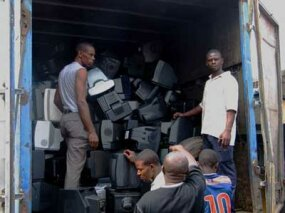 Workers in Lagos, Nigeria, unload imported TVs and PC monitors, most of which will be sent to the local dumps. From there, they will be scavenged for recycling and then burned. ­