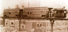 This circa 1877 view of a New York Elevated Railroad train is notable for the decorous steam dummy locomotive no. 18, Brooklyn, built by Brooks Works that year. These machines had centrally-located cylinders and a water tank atop the boiler.