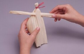 Stick the arms through two holes in the corn husk.