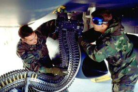 Airmen load ammunition for the F-15's 20-mm cannon.