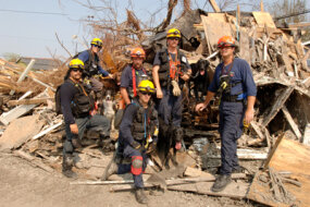 FEMA Urban Search and Rescue Task Force members pose with their rescue dogs in a neighborhood impacted by Hurricane Katrina.