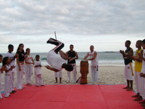 Capoiera, a mix of martial arts and cultural elements, being performed on the beach in Brazil.