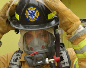 An Army National Guard firefighter puts on his SCBA (self-contained breathing apparatus) and helmet.