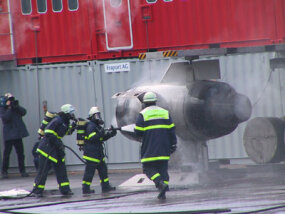 Airport firefighter trainees put out a simulated engine fire.