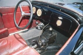 The Frank Mack T has an exposed transmission and driveshaft between the driver and passenger seats.