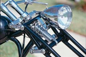 Stretched girder forks give this chopper its name, pivoting up and down on short arms to compress a coil-over shock mounted behind the headlight.