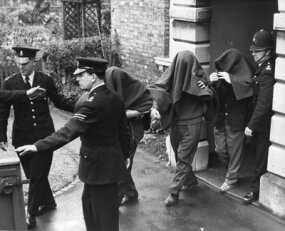 Three of the suspects arrested in connection with the Great Train Robbery are photographed leaving Linslade court with blankets over their heads.