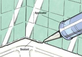 Run a bead of caulk between the tub and first row of tiles.