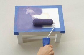 Use a foam roller to paint the top of the stool Purple Dusk.