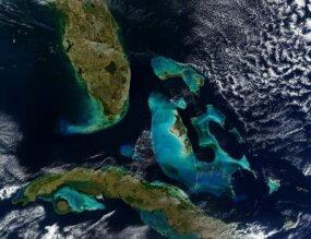This image from a NASA satellite shows the coastline of the Bahamas, Florida and Cuba. The banks are shallow coral reefs that reflect light through the ocean, giving it a bright blue color.