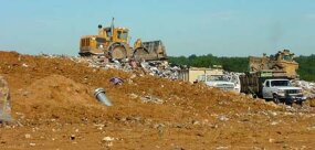 A bulldozer prepares a new cell in a landfill