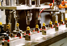 Machines assemble components that require several pieces, like minifigures