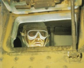 An M-3 Grant/Lee Medium Tank driver peers through the raised driver's hatch, which is in the hull just below, and to the left of, the 37mm turret gun.