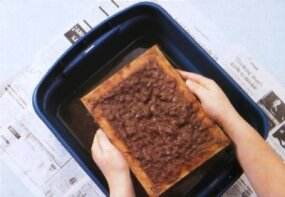 Hold the frame over the pan and let the pulp drain.