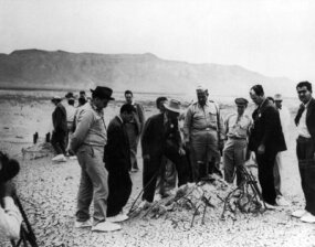 Manhattan Project officials, including Dr. Robert J. Oppenheimer (white hat) and General Leslie Groves, inspect the detonation site of the Trinity atomic bomb test.