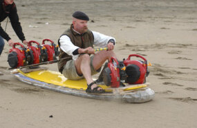 MythBuster Jamie Hyneman drives his yellow surfboard/hover craft with fans attached to the front and rear of the board at Ocean Beach.