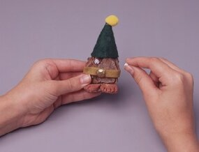 Glue wiggly eyes on and add other facial features to your elf.
