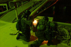 Naval Special Warfare operators inspect a shipping container at Iraq's Mina Al Bakar Oil Terminal during an operation to secure the oil platform from being destroyed by Iraqi military.
