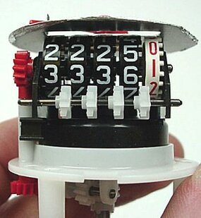Each dial is then turned by pegs on the previous dial through a small helper gear (white).