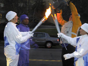 Torchbearer Stephanie Stockman, an employee in the NASA Laboratory for Terrestrial Physics in Maryland, passes the flame to the next runner.