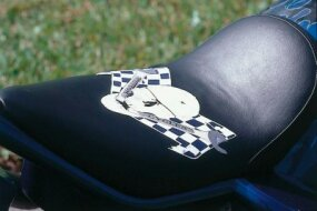 Skull logo of The Wrench Custom Cycles appears on the seat.