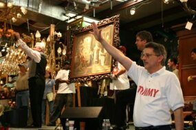Auctioneers guide the sale of one of the pieces of art auctioned at Red Baron's Antiques.