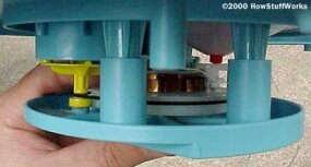 The yellow governor can be seen inside a cylinder molded into the blue plastic.