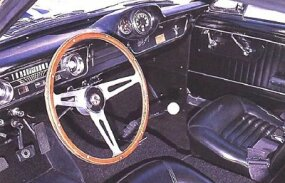 A wood-rimmed wheel, extra gauge pod, wide seat belts, and side-exit exhausts were standard on the Shelby GT-350.