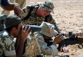 German and American snipers work together to sight a shot in desert training exercises.
