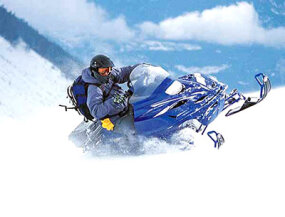 This snowmobiler leans into a sharp turn, which helps to keep him from flipping.