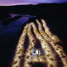 Martin Lockley stands with a series of parallel dinosaur tracks along Purgaoire River, Colo.