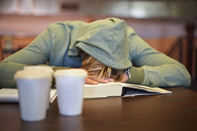 student asleep on books
