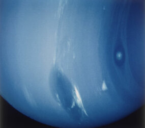 The Great Dark Spot on the surface of Neptune, as observed by the Voyager 2 spacecraft in 1989. The spot, thought to be a swirling mass of gases, had disappeared by 1994, to be replaced by a similar spot in a different location.