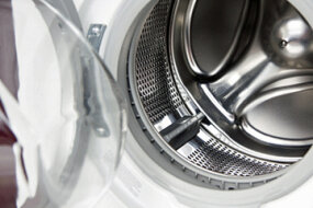 A front-loading washing machine, empty, with one of the paddles visible