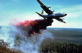 An air tanker drops water and fire retardant onto a wildfire.