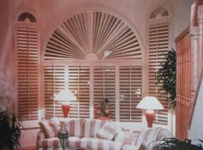 © Shutters unify this arrangement of a large central window flanked by tall, thin side windows. A custom sunburst design repeats at the tops of the three windows.