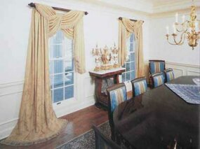 © A formal dining room drapery uses classic damask fabric to cross-tie in a swagged valance before falling off to a shorter length at one side.