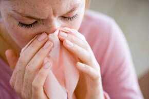 Woman blowing her nose with tissue