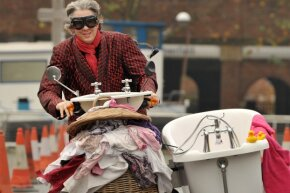 """British inventor Edd China take a triumphant spin on the world's fastest """"toilet"""" during a race at the annual Guinness World Records Day in London on Nov. 17, 2011."""