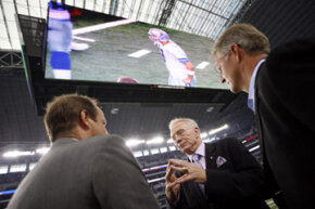 Dallas Cowboys owner Jerry Jones and two other men talk underneath the new giant HDTV in Cowboys Stadium on Aug. 21, 2009.