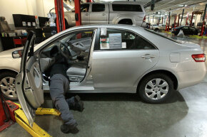 Toyota service technician Tungyio Saelee performs a recall repair on an accelerator pedal from a brand new Toyota Corolla at City Toyota on Feb. 5, 2010, in Daly City, California.