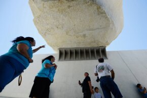"Visitors stand beneath the ""Levitated Mass."""